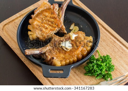 Tasty marinated grilled pork cutlets with roasted garlic cloves served in a griddle pan on a wooden board with a sprig of fresh parsley - stock photo
