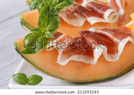 Tasty melon with ham and basil close-up on the table. horizontal  - stock photo