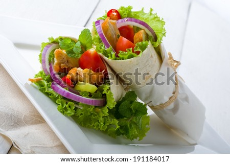 Tasty Mexican chicken tortilla or corn tacos with a healthy grilled chicken and salad filling served on a plate for a lunchtime snack - stock photo