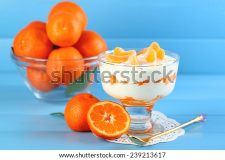 Tasty milk dessert with fresh tangerine pieces in glass bowl, on color wooden background - stock photo