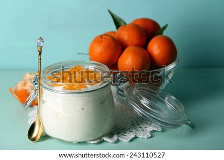 Tasty milk dessert with fresh tangerine pieces in glass jar, on color wooden background - stock photo