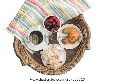 Tasty morning breakfast on a wicker tray with freshly baked pastries filled with cheese, strawberry and peach, a croissant with chocolate hazelnut spread, coffee and fresh berries, overhead on white  - stock photo