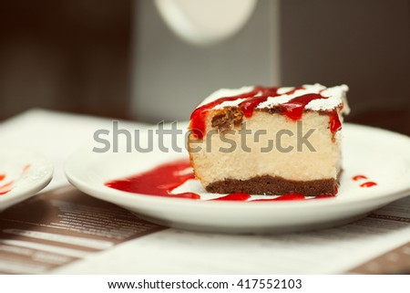 Tasty morning cafe. Slice of cheese cake with sugar powder and strawberry jam in cafe. Daylight. Close up. Copy-space. Outdoor shot - stock photo
