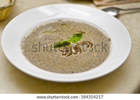 tasty mushroom soup with champignons in white plate on the table - stock photo