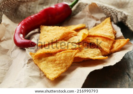Tasty nachos and chili pepper on paper, on wooden background - stock photo