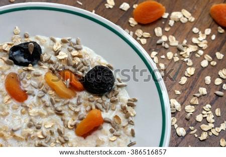 Tasty oatmeal porridge on a dark rustic table closeup - stock photo