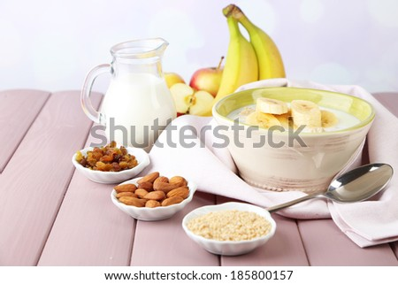 Tasty oatmeal with bananas and milk on table on bright background - stock photo