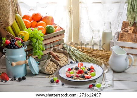 Tasty oatmeal with fresh fruits and milk - stock photo