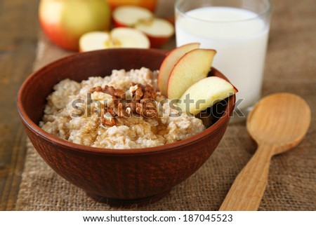 Tasty oatmeal with nuts and apples on wooden table - stock photo