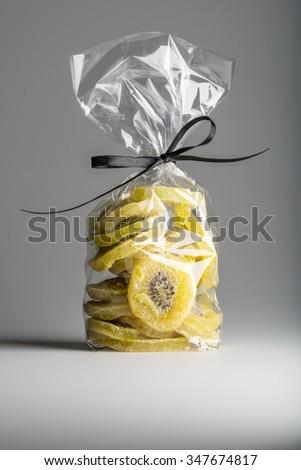 Tasty organic candied kiwi slices into luxury transparent plastic bag isolated on grey background. Elegant gift with elegant black ribbon. Shooting in studio. - stock photo