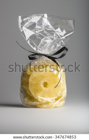 Tasty organic candied pineapple slices into luxury transparent plastic bag isolated on grey background. Elegant gift with contemporary black ribbon. Shooting in studio. - stock photo