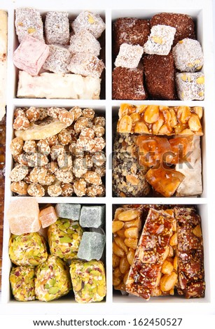 Tasty oriental sweets in wooden crate, close up - stock photo