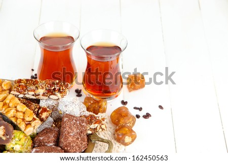 Tasty oriental sweets on tray and glasses of tea, on white wooden background - stock photo