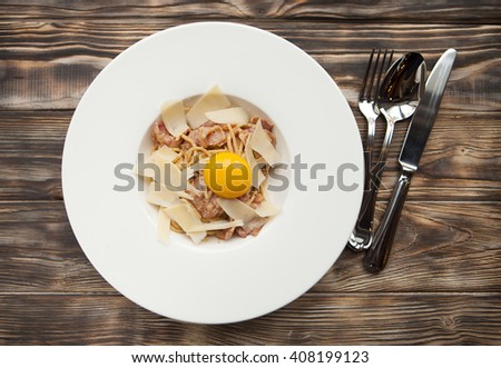 Tasty Pasta Carbonara on white plate with parmesan and yolk on dark wooden background - stock photo