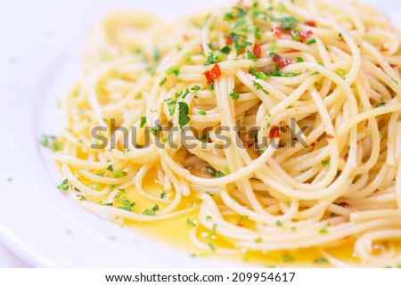 Tasty pasta on white plate in the restaurant, traditional Italian meal, delicious spaghetti with paprika and basil, gorgeous Mediterranean food concept  - stock photo