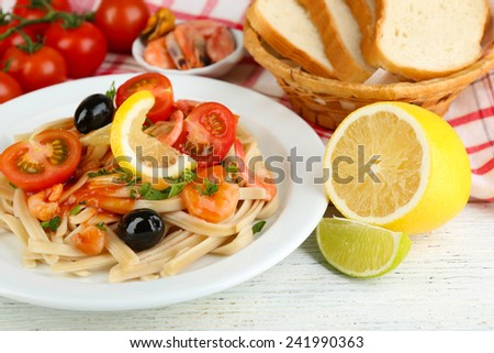 Tasty pasta with shrimps, black olives and tomato sauce on plate on wooden background - stock photo