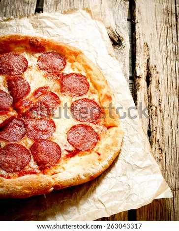 Tasty pepperoni pizza on an old paper. On a wooden background. - stock photo