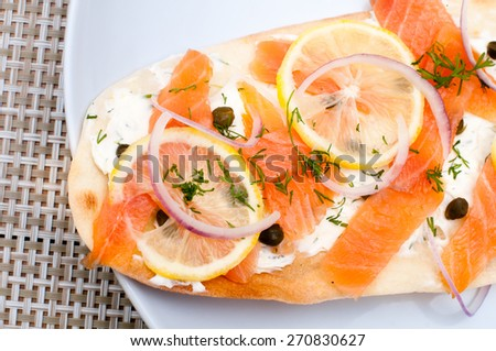 Tasty personal flat bread pizza is topped with an herb cream cheese spread, smoked salmon, slices of paper thin sliced lemon, red onion and then sprinkled with dill and capers. It has a cracker crust. - stock photo