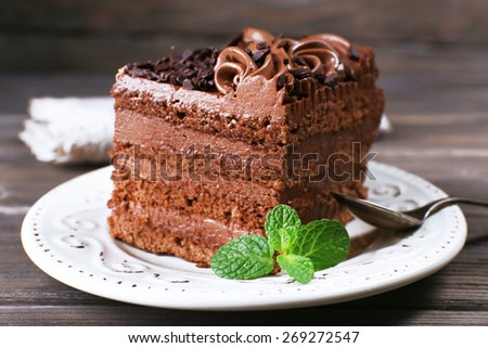 Tasty piece of chocolate cake with mint on wooden table background - stock photo