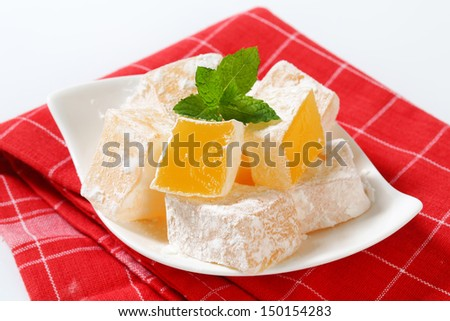 Tasty pieces of orange turkish delight on a porcelain tray - stock photo