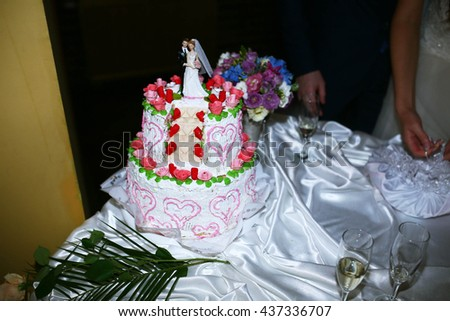 tasty  pink white wedding cake decorated with hearts, sculpture of bride and groom on top - stock photo