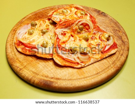 Tasty pizza on a wooden plate. Traditional healthy food from Italy. - stock photo