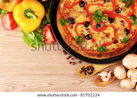 tasty pizza on the plate and vegetables on a wooden background - stock photo