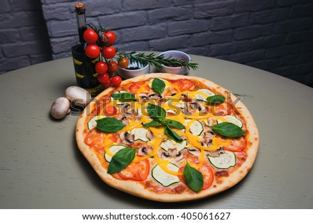 Tasty pizza vegetarian with mushrooms, zucchini, tomatoes, pepper and basil - stock photo