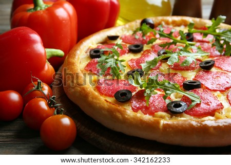 Tasty pizza with salami on decorated wooden table, close up - stock photo
