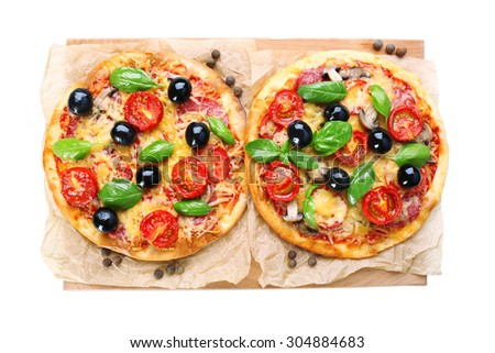 Tasty pizza with vegetables and basil on cutting board close up - stock photo