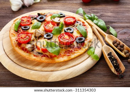 Tasty pizza with vegetables and basil on table close up - stock photo
