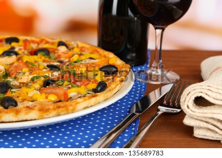 Tasty pizza with wine on wooden table on room background close-up - stock photo