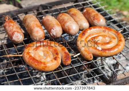 Tasty pork and beef sausages cooking over the hot coals on a barbecue fire - stock photo
