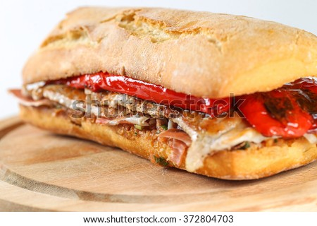 Tasty pork grilled serranito sandwich in a ciabatta with ham and red pepper on a white background - stock photo