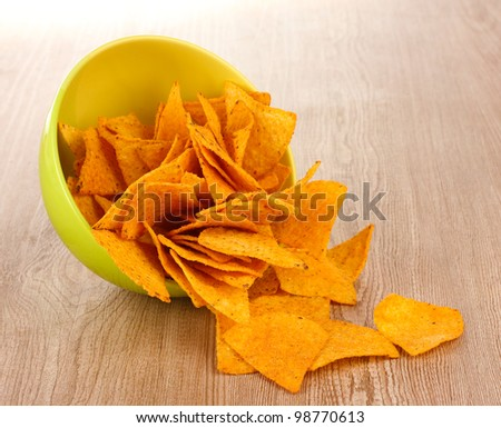 tasty potato chips in green  bowl on wooden table - stock photo