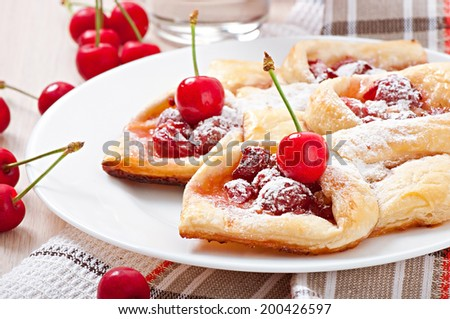 Tasty puff with a sweet cherry - stock photo