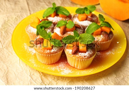 Tasty pumpkin muffins on brown paper - stock photo