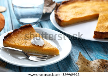 Tasty pumpkin pie on plate on a blue wooden table - stock photo