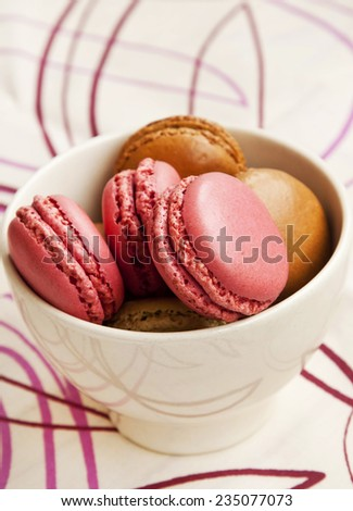Tasty Raspberry and Pistachios Macarons Filled with Cream Placed in a Bowl - stock photo