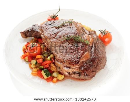 Tasty ribeye steak with stir fried vegetables isolated on white background - stock photo
