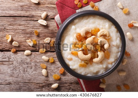 Tasty rice pudding with nuts and raisins in a bowl close-up on the table. Horizontal view from above