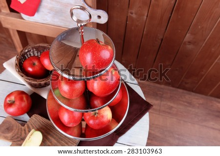 Tasty ripe apples on serving tray on table on wooden background - stock photo