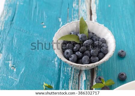 Tasty ripe blueberries in bowl on blue wood floor - stock photo
