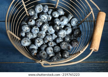 Tasty ripe blueberries in metal basket, on wooden background - stock photo