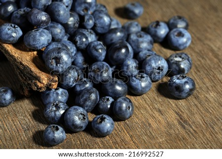 Tasty ripe blueberries, on wooden background - stock photo
