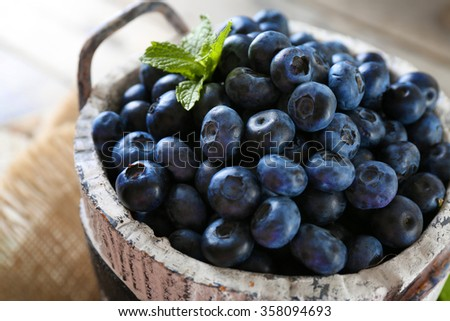 Tasty ripe blueberries with green leaves in bucket on table close up - stock photo