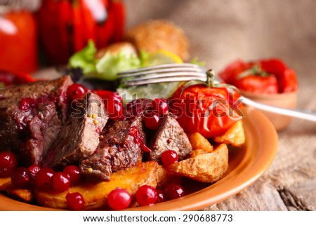 Tasty roasted meat with cranberry sauce, salad and roasted vegetables on plate, on wooden background - stock photo
