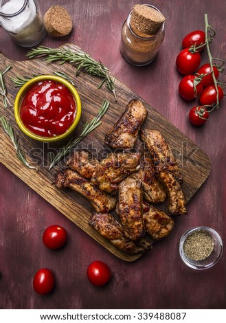 tasty roasted ribs with spicy sauce and herbs on a cutting board on wooden rustic background top view close up - stock photo