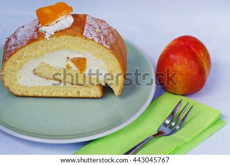 Tasty roll cream cake dessert with peach on soft green plate, fork on green napkin on white background.  - stock photo
