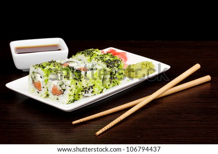 Tasty rolls served on white plate with chopsticks on wooden table on black background - stock photo